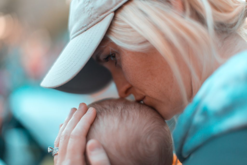 Woman Kissing Baby - Limiting Stories Can Keep us From happiness