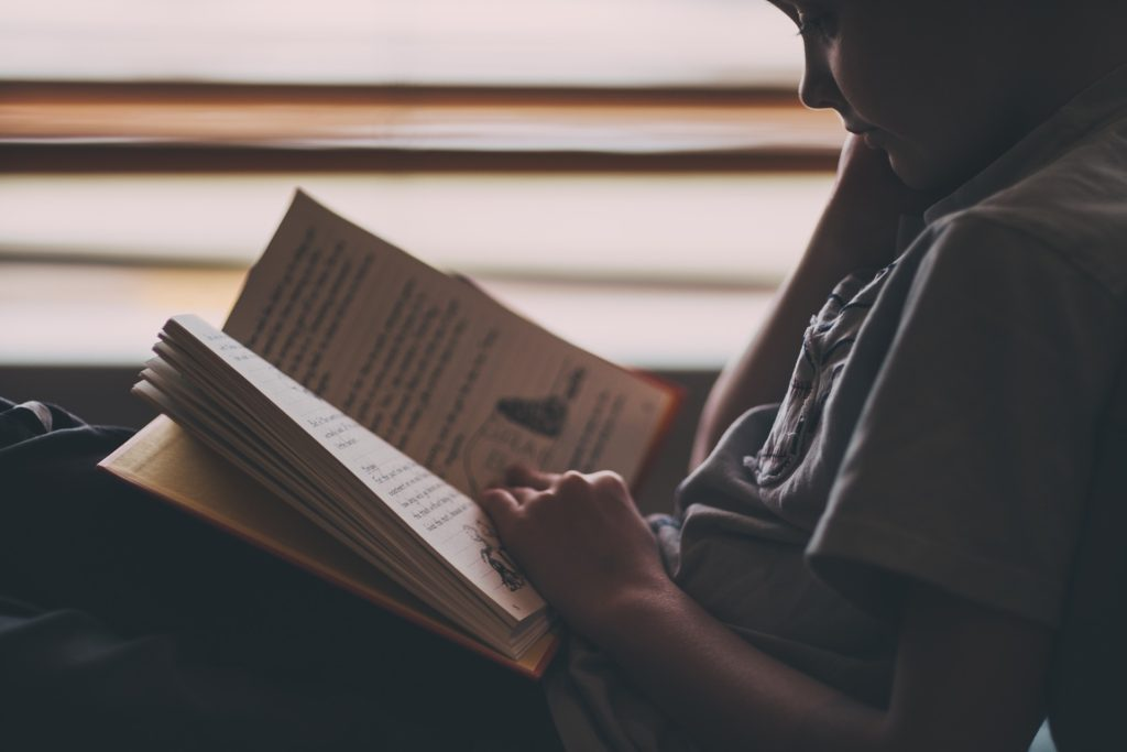 Boy Reading - Redshirting your child for academic or social needs is a tough decision for moms.