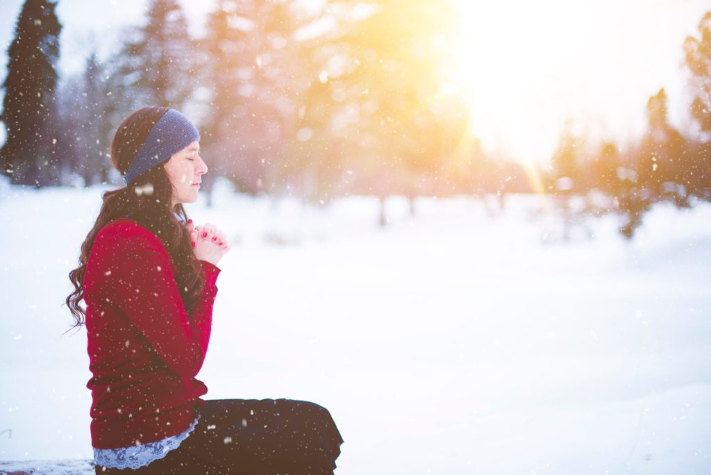Woman meditating in snow - Stress Holidays